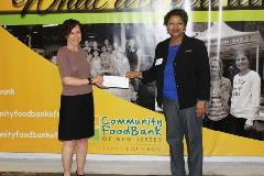 Holding check for $1,500 donation to The Community FoodBank of New Jersey